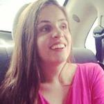 Fotografia de perfil em plano médio. Mulher. Pele branca, rosto quadrado; cabelos lisos, castanhos, longos. Esboça um sorriso largo. Usa blusa rosa pink com gola V. Fim da audiodescrição.